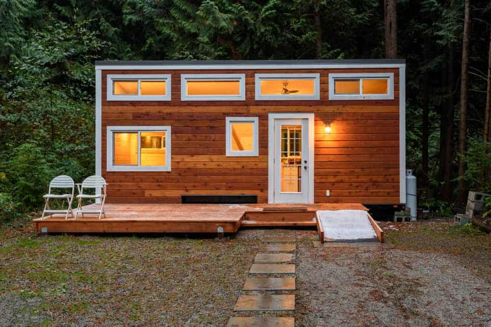 Tiny cabin with wood exterior and white trim. The front door steps out onto a small deck.