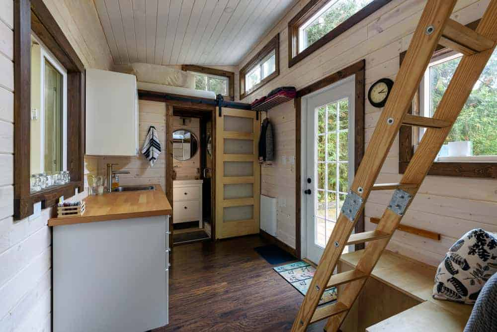 Interior main living space of a tiny cabin with kitchen area and two loft bedrooms accessible by ladders.