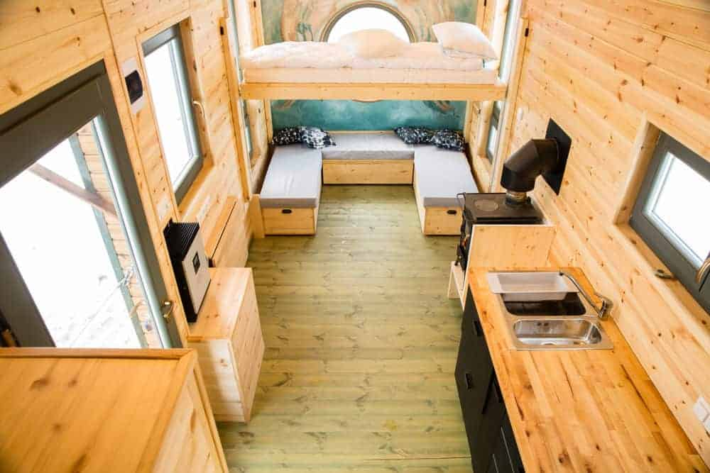 Beautiful and spacious interior of a tiny house with kitchen, loft bed and u-shaped sofa bench in the living room.