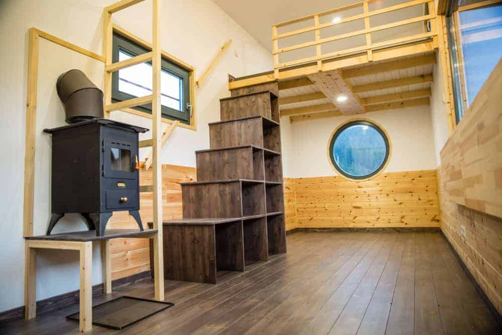 Storage cube-stairs lead up to sleeping loft area in this tiny house with wheels. Notice the round window which looks great and brings in light.