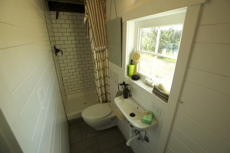 Photo of a sizable bathroom inside a tiny house - includes floating sink, toilet and shower.
