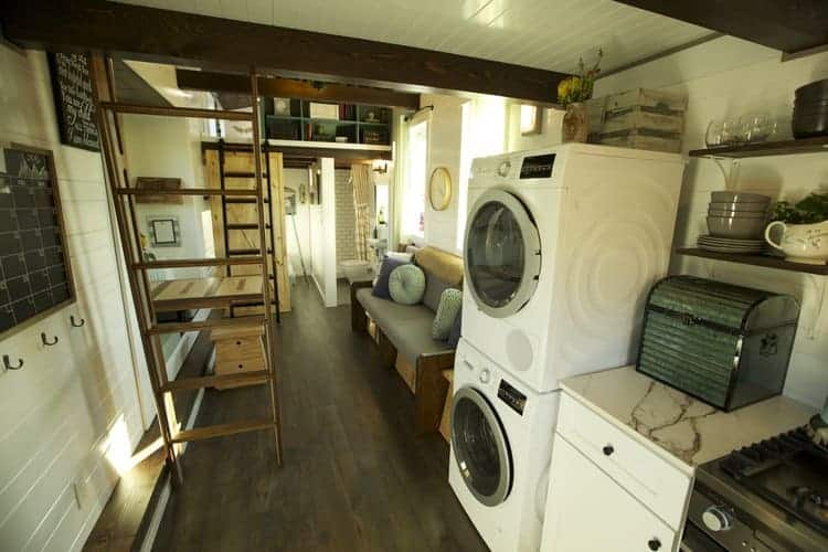 Stackable washing machine and dryer inside a tiny house with dark wood flooring.