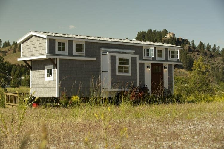 """Exterior photograph of a long """"two-story"""" tiny house with slide-out."""