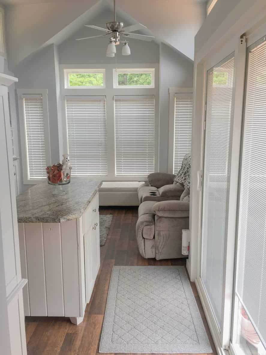 Living room area in the front of a tiny house which is next to the kitchen that features a small island (unusual for a tiny home).