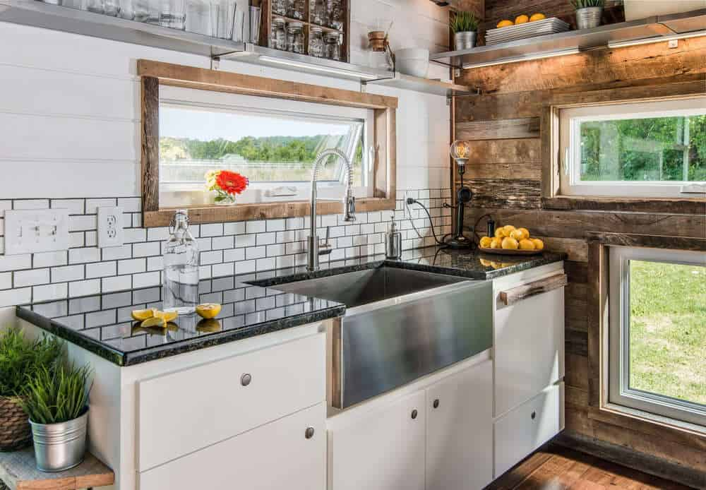 Check out the distressed wood accent wall on the end of the kitchen. It actually looks great with the white subway tile which is tied in with the distressed window frame. Stainless steel shelves span the entire length of the kitchen up above.