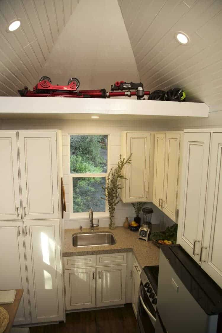 Here's a tiny house kitchen with loads of storage including a full pantry cabinet. Storage is a premium in any small living space so I'm sure this tiny house kitchen design will appeal to many people for that reason alone. I'm not wild about the countertop color, but otherwise, I like this kitchen.