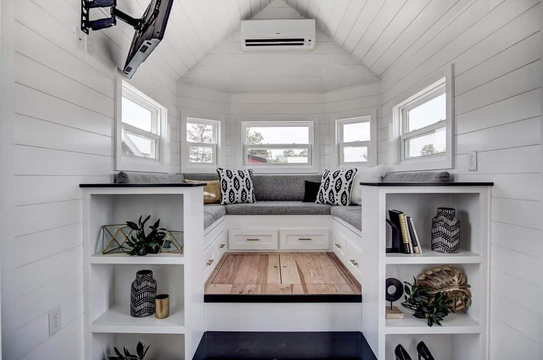 Tiny house living room elevated with built-in sectional sofa and storage