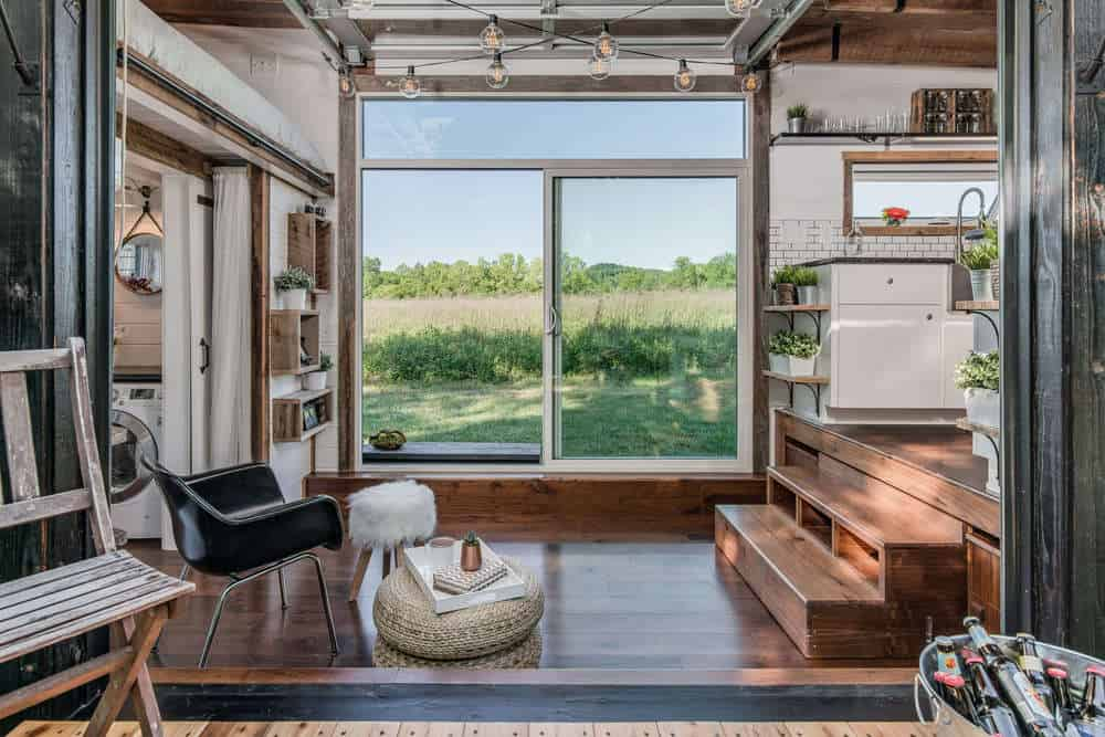 Tiny house living room with armchar opening up onto a deck