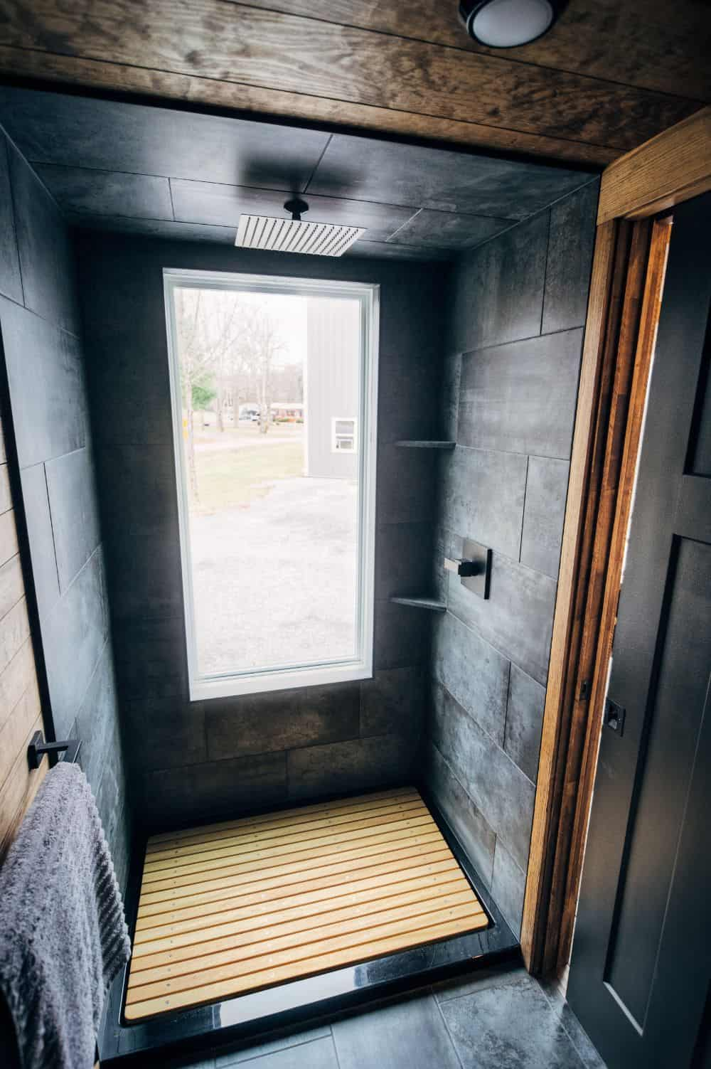 Walk-in shower with large window and wood floor with dark gray tile. This particular shower enjoys a rain shower head.