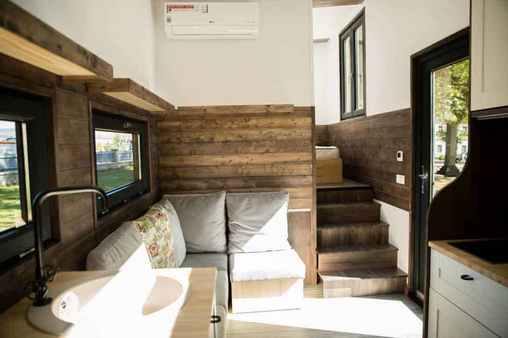 Small living room area next to stairs inside tiny home.