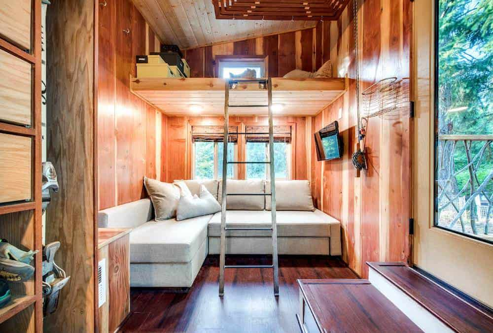 Tiny house with white chaise lounge sectional sofa under bedroom loft with stunning wood walls