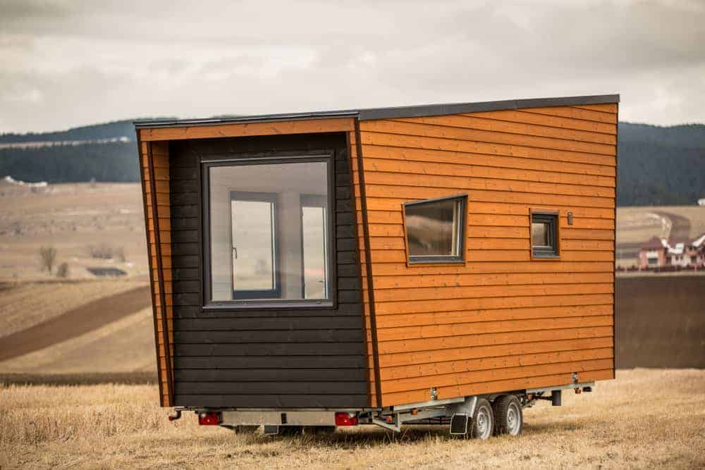 Very tiny house on wheels with large picture window on one end (where the living room area is).