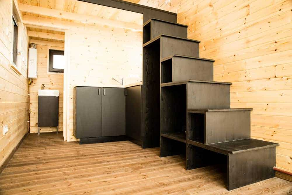 Storage shelf stairs leading to the loft sleeping area in a tiny house on wheels. There's a tiny l-shaped kitchen under the stairs.