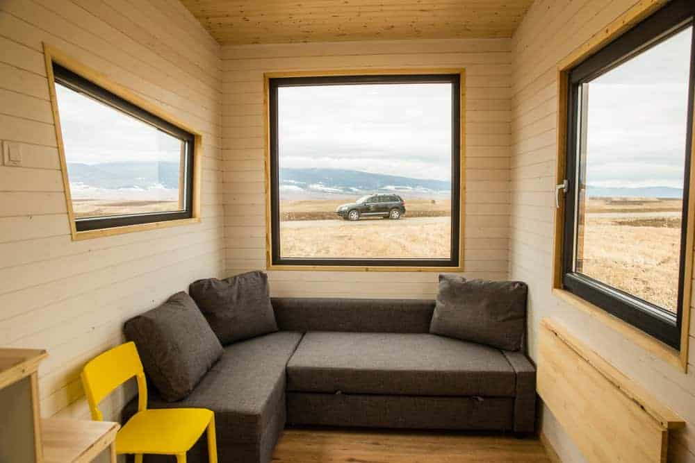 L-shaped sectional bench sofa in a tiny house with large windows that bring in plenty of light.
