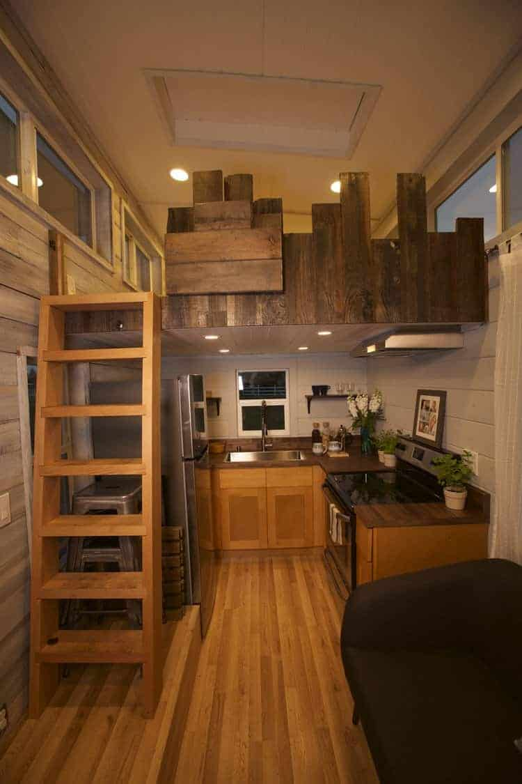 Here's a gorgeous mid-tone wood u-shaped kitchen in a tiny house on wheels. The kitchen is almost entirely under the loft area so watch your head. It includes recessed lighting, a large sink, full fridge and range.