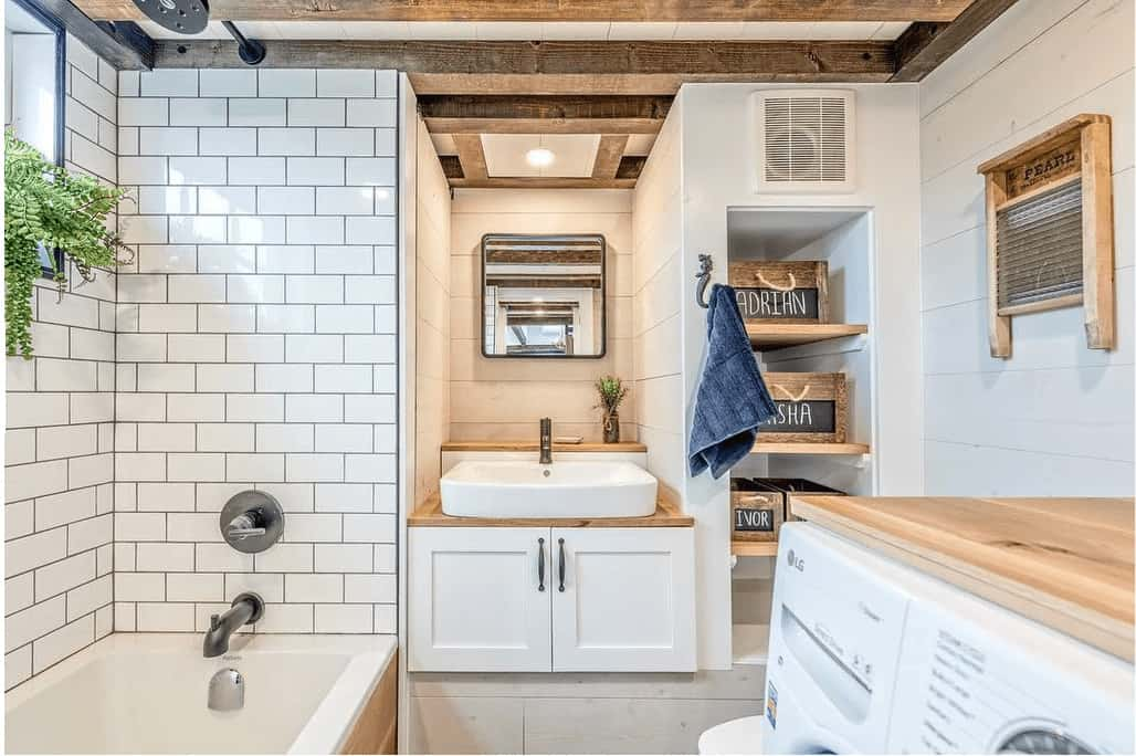 Here's a spacious tiny house bathroom with built-in tub, washing machine, dryer, toilet and sink.