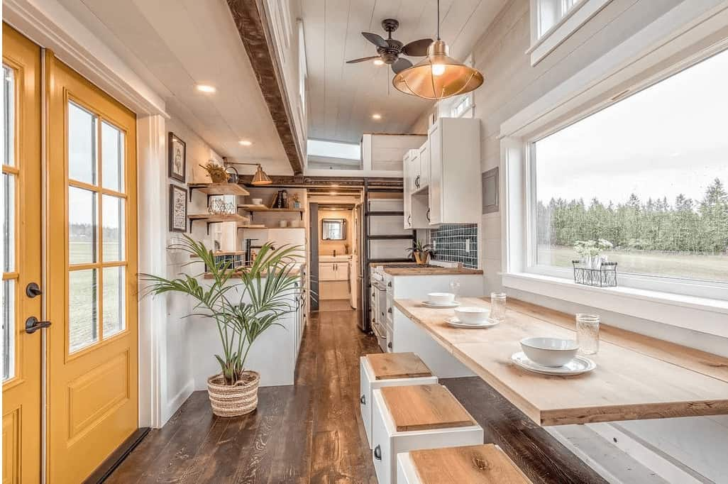 I love this feature in this tiny house - it's a long breakfast bar-style dining table that accommodates 3 people very comfortably.