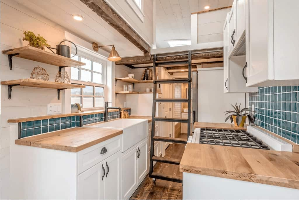 Galley style kitchen with white cabinets and light wood counter top. This kitchen includes a large farmhouse sink and full range.