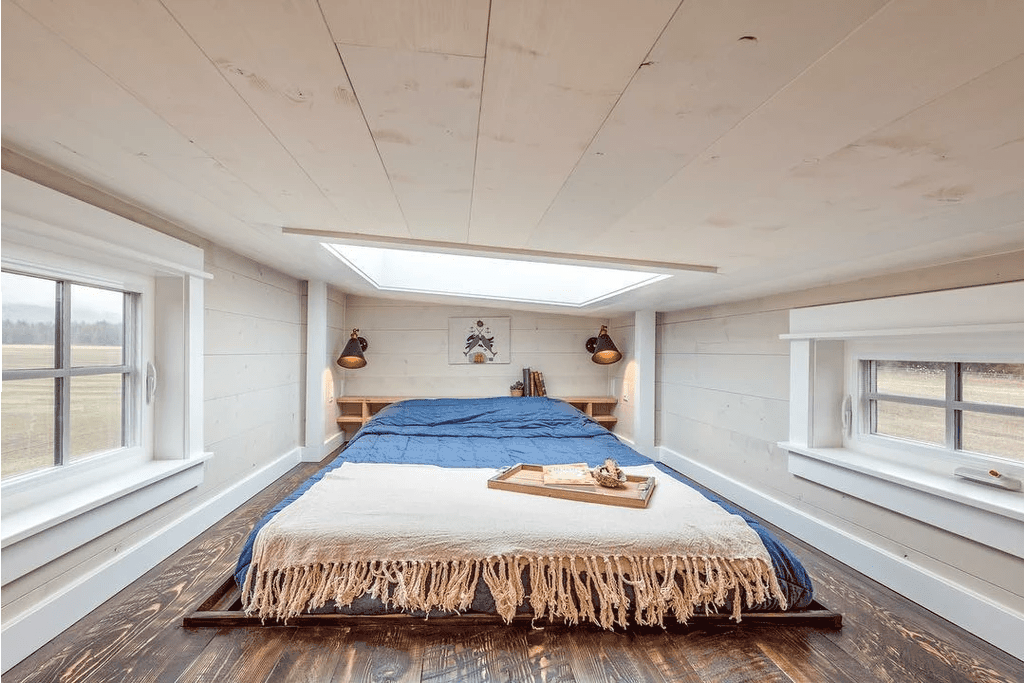 The clearance is generous in this tiny house loft bedroom and is well-lit with a large skylight.