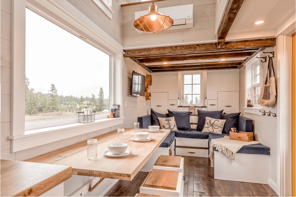 The open concept living space includes a breakfast bar dining table and full-width sofa with plush pillows.