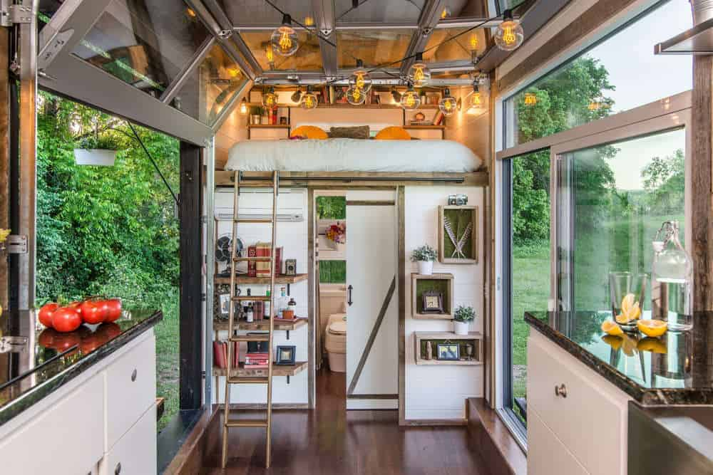 Loft area of tiny home accessible by space-saving ladder.