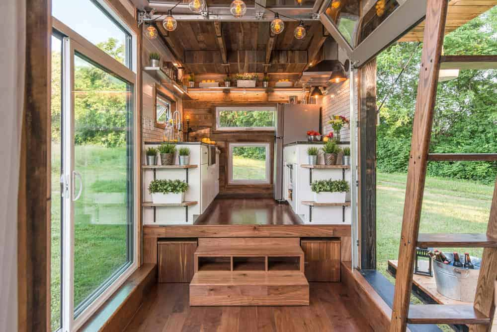 Interior photo of a tiny house with sunken living room, galley kitchen and huge picture windows.