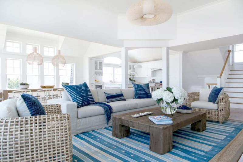 This living room has the spirit of the sea within its brilliant blue patterned area rug and blue pillows that go quite well with the light gray sofa and pair of woven wicker armchairs. These are all brightened by the brilliant white ceiling that hangs a decorative woven wicker pendant light.
