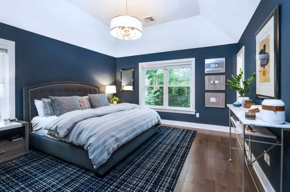 Large primary bedroom with stylish dark blue walls and a handsome bed frame set on the attractive rug covering the hardwood flooring.