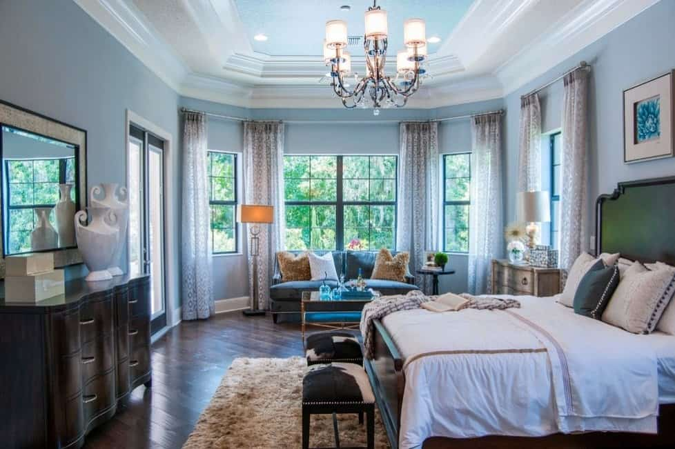 This primary bedroom offers a stunning ceiling lighted by a gorgeous modern chandelier.