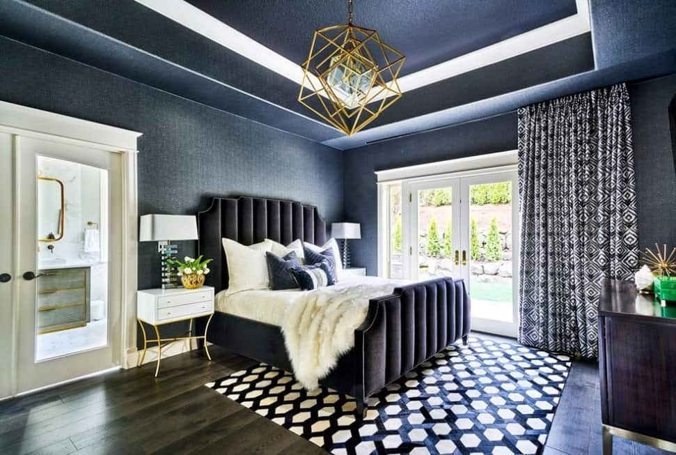 A primary bedroom covered by stylish blue walls and ceiling lighted by a glamorous ceiling light. The bed frame is so handsome-looking as well.