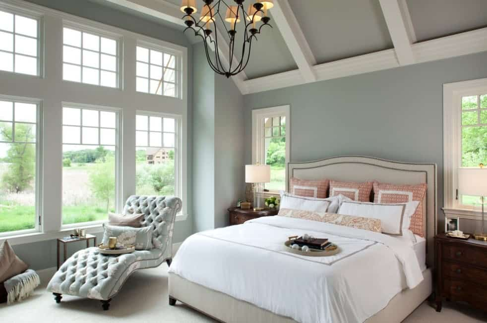 A classy primary bedroom featuring blueish gray walls and ceiling with beams along with carpet flooring.