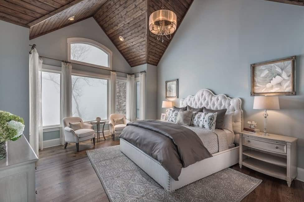 Large primary bedroom featuring a stunning wooden ceiling matching the hardwood flooring.