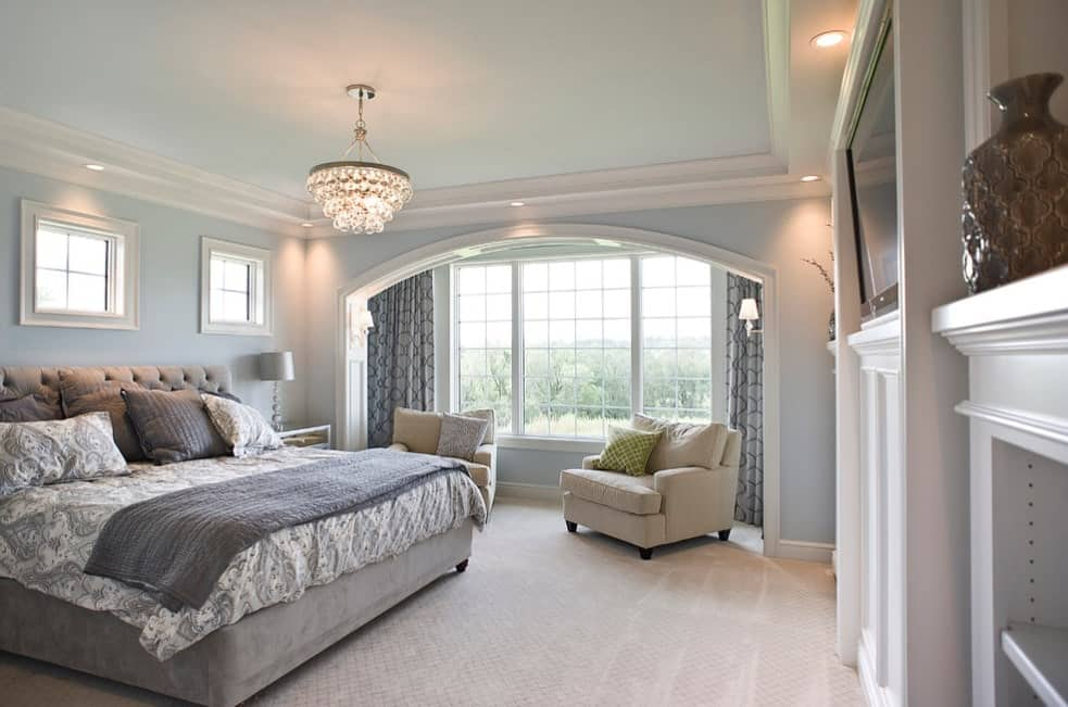 A large primary bedroom featuring a luxurious gray bed set on the carpet flooring. The room is lighted by a gorgeous chandelier hanging from the tray ceiling.
