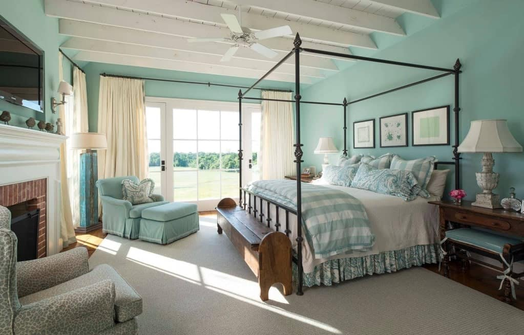 A classy primary bedroom featuring blue-green shades all over the room. The hardwood flooring is topped by a large traditional rug.