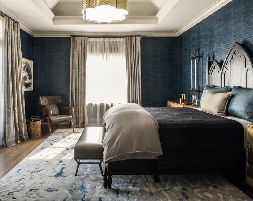 A classy primary bedroom with blue elegant walls surrounding the place. The stunning tray ceiling houses the large and gorgeous pendant lighting.