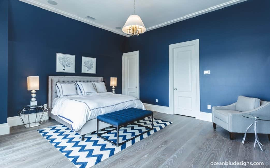 Large primary bedroom with stylish blue walls and hardwood floors, along with a modish bed and seat.