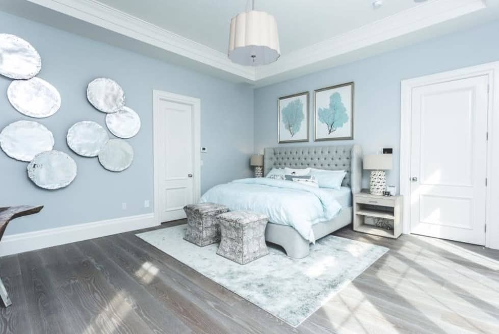 Large primary bedroom featuring rustic hardwood flooring and light blue walls with multiple stylish wall decors.