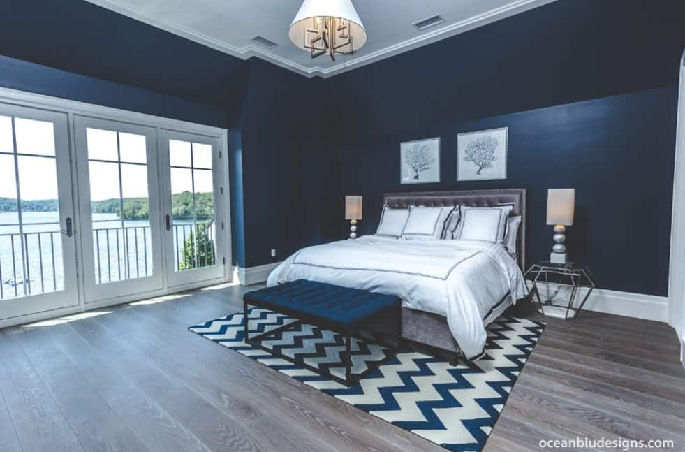 Spacious primary bedroom featuring rustic hardwood flooring and handsome blue walls that look so elegant. There's a doorway as well, leading to the home's private balcony offering magnificent outdoor views.