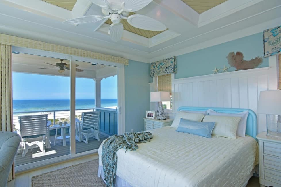 This primary bedroom features light blue walls and a stunning ceiling, along with a doorway leading to the patio overlooking the jaw-dropping ocean view.