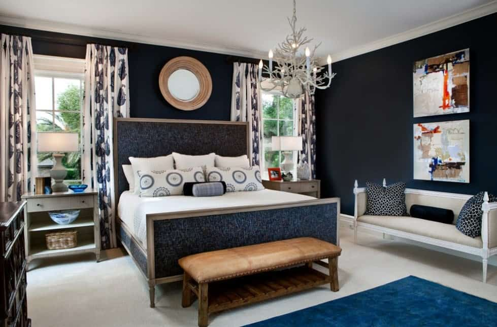 Small primary bedroom with a handsome bed frame surrounded by an elegant blue accent and lighted by a glamorous chandelier.