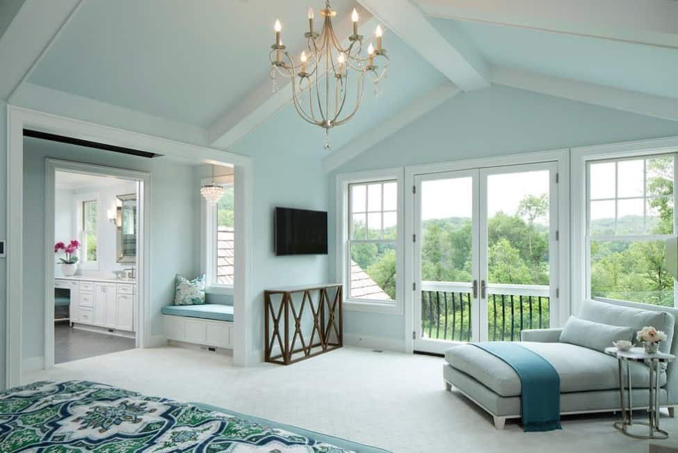 A large primary bedroom featuring light blue walls and white carpet flooring topped by a charming green rug.