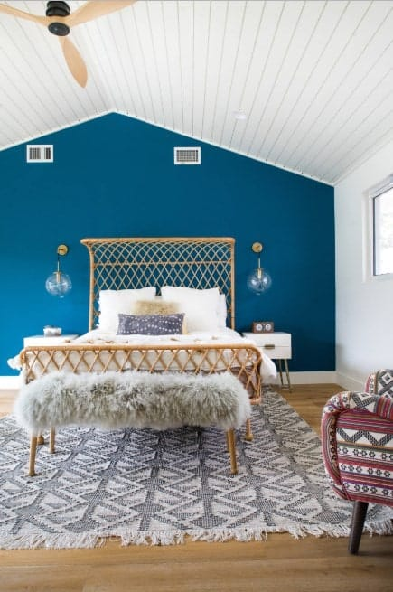 This primary bedroom boasts white and blue walls and a white vaulted ceiling together with the hardwood flooring topped by a classy rug.