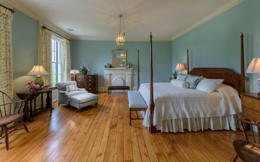 Large primary bedroom with blue-green walls and hardwood flooring, along with elegant window curtains.
