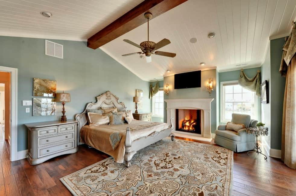 Large primary bedroom featuring a luxurious bed and an elegant rug covering the hardwood flooring. There's a classy fireplace keeping the room warm.