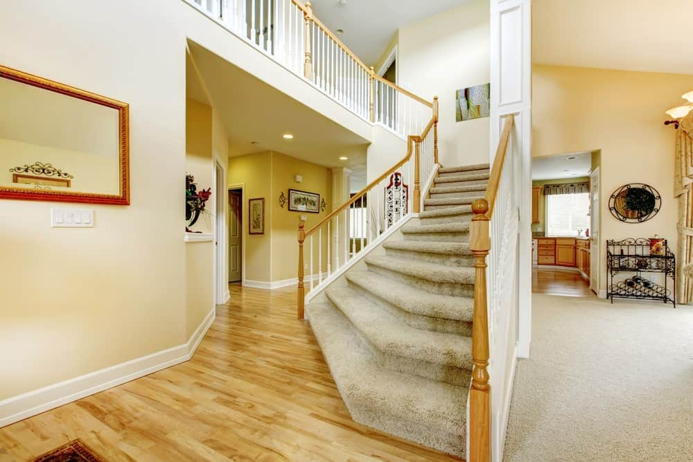 This home features hardwood floors and beige walls, along with a staircase featuring full carpet floors.
