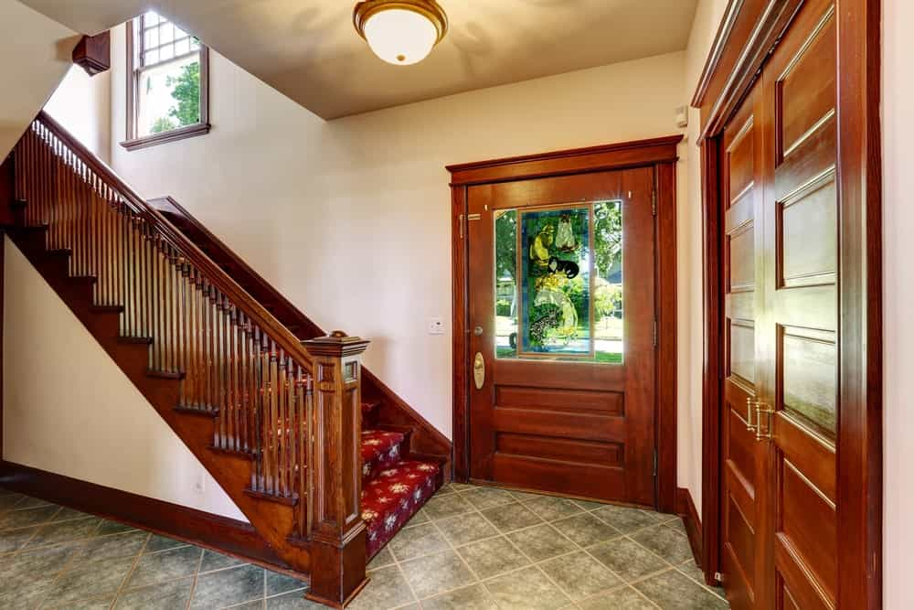 A small home entry with a staircase boasting attractive red carpet floors with hardwood rails.