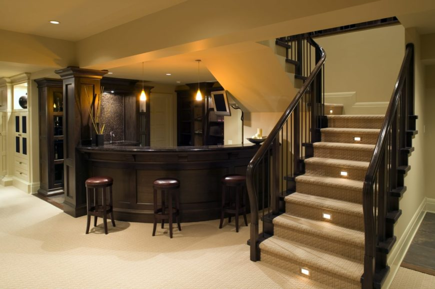 This home boasts a large bar area that looks elegant near the home's L-shape staircase with carpet floors.