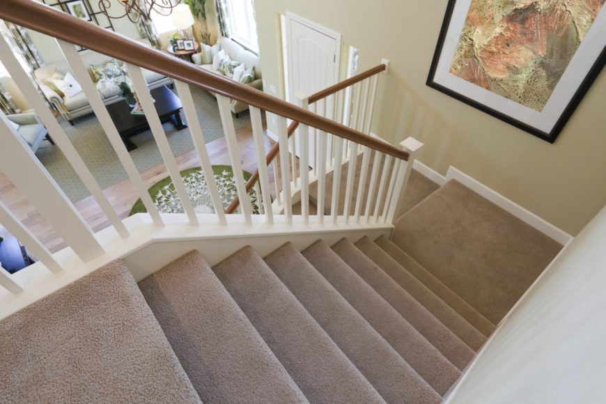 A small home entry with formal living space and an L-shaped staircase with full carpet floors and white railings.
