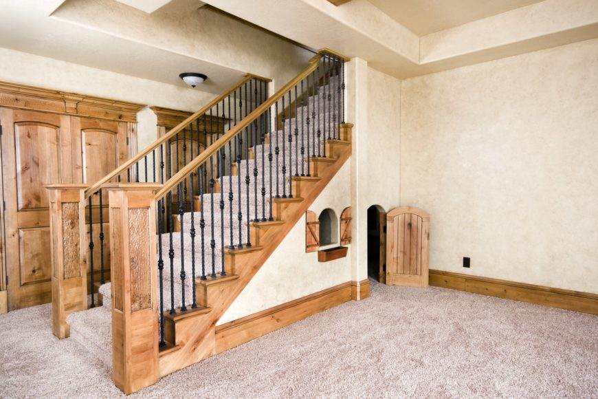 A very attractive storage staircase with carpet floors and wooden handrails with black iron railings.