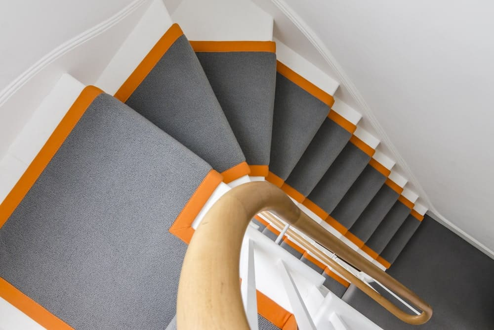 This home boasts a stylish staircase with gray carpet floors with an orange shade on each side.